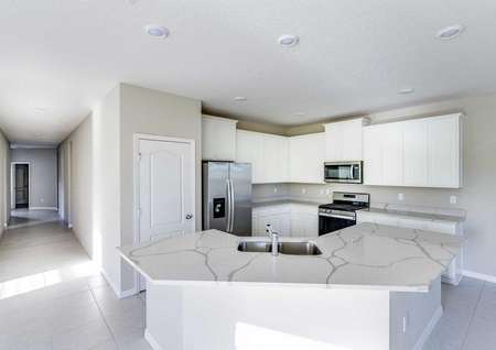 Kitchen in the Mykka floor plan with an island, tile flooring and a view of the plans hallway.