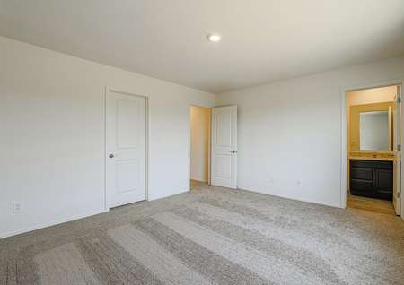 Spacious master bedroom with tan carpet and an attached bathroom.