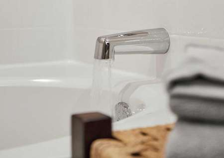 Bath tub spout with water running.