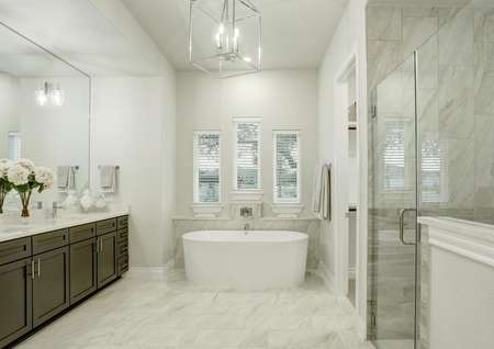 Staged master bath with white freestanding tub, luxury lighting and white tile floors.