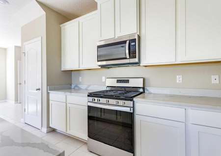 Kitchen area with a gas range stove, quartz countertops, white cabinets and a stainless steel and black microwave.