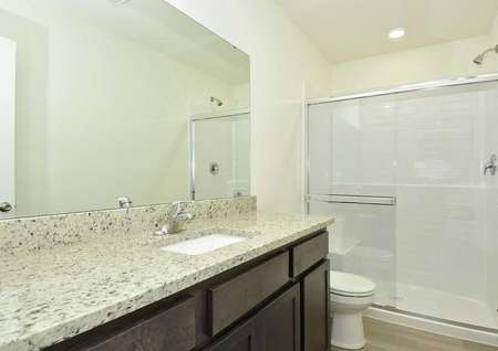 Cypress bathroom with granite countertops, extended vanity mirror, and brown cabinets