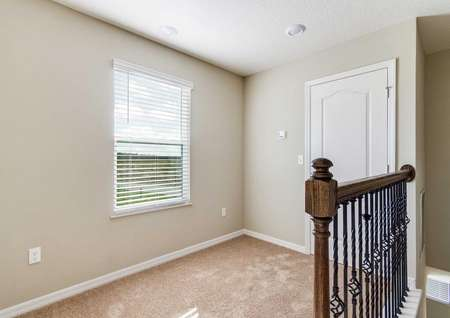 The upstairs game room in the St. Johns floor plan that has a window, a closet and light brown carpet.