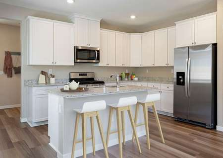 Staged kitchen with white cabinetry, stainless steel appliances and white bar stools.
