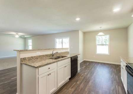 Hartford kitchen and dining nook with dark tile floors, recessed lights, and granite counter island with sink