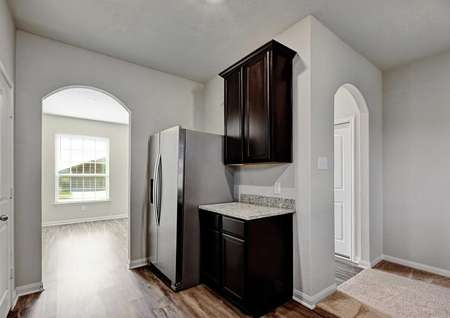 Fannin completed kitchen with stainless steel refrigerator, gray walls, and brown cabinets with granite tops