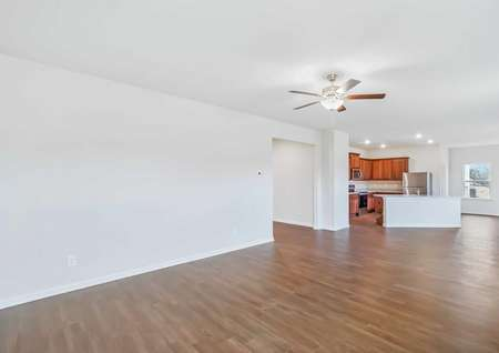 Family room with luxury vinyl plank flooring leading to a full kitchen and a dining room.
