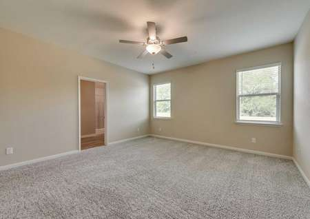 The master bedroom in the Texoma floor plan with two-windows, light-brown carpet, white baseboards and tan walls.
