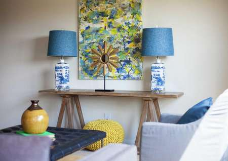 Driftwood model home staged living room with two decorative lamps with blue shades on a wooden table, painting hanging on the wall, and a yellow vase on a navy coffee table