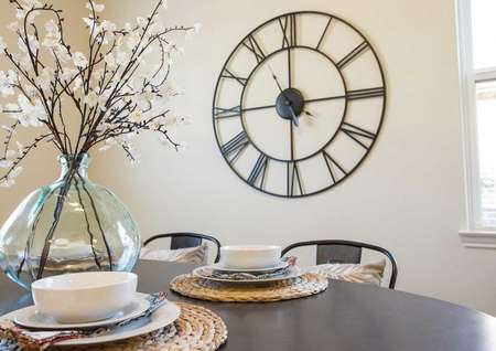 Wooden table with placemats, white bowls and glass ornament with flowers plus large wall clock in the back.