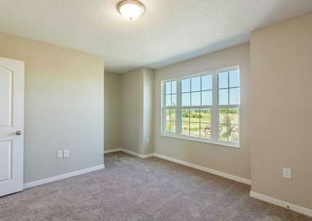 Secondary bedroom in the Calabria floor plan with light brown carpet, tan walls and white baseboards.