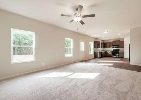 Hartwell great room with carpet flooring in the family room, hardwood floor in the kitchen and dining area, and multiple backyard windows