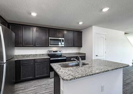 Kitchen comprised of granite countertops, stainless steel appliances, upper-wood cabinets and vinyl wood floors.