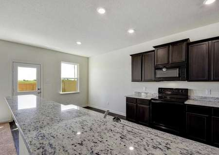Mesquite kitchen with can lights, dark brown cabinets, and white spotted granite countertops
