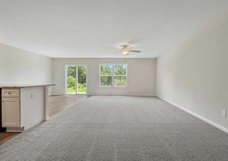 Allatoona great room with overhead ceiling fan, light color carpet, and sliding patio doors