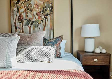 Bed with pink and tan linens and side table with a white lamp