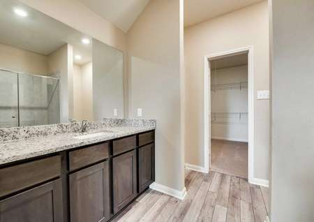 Houghton plan's master bathroom with an open door that gives a view of the walk-in closet.