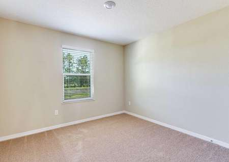 A spare bedroom in the Wekiva floor plan with light brown carpet, white baseboards and tan walls with a window on one of them.