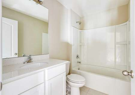 A secondary bathroom in the Tomoka floor plan that has a tub/shower combo, quartz countertops and white cabinets.