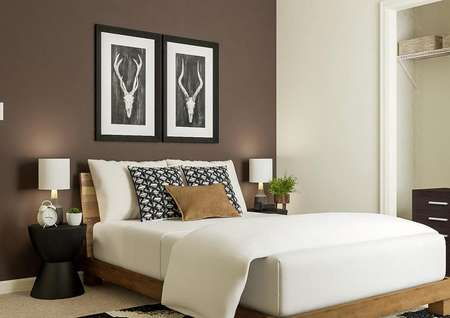 Rendering of a secondary bedroom with a   closet and a wood frame bed with black nightstands against a dark accent   wall.