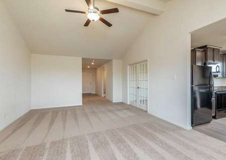 Sabine great room with carpeting in the family room, black appliances in the kitchen, and overhead lighting