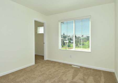 Cypress bedroom with private bathroom, white window frame and trim, and brown carpet