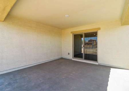 The covered back patio in the Guadalupe floor plan that has a sliding glass door and a light on the ceiling.