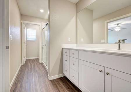 The Kennedy floor plan's master bathroom with a walk-in shower, cultured marble countertops and wood-like floors.