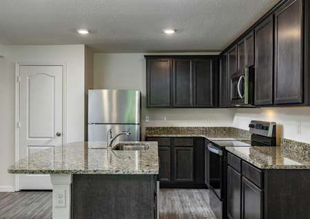 Fully-loaded kitchen featuring tall, upper-wood cabinets, granite countertops and stainless steel appliances.