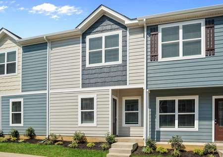 The Pine plan has tan siding with a dark blue shake siding accent.