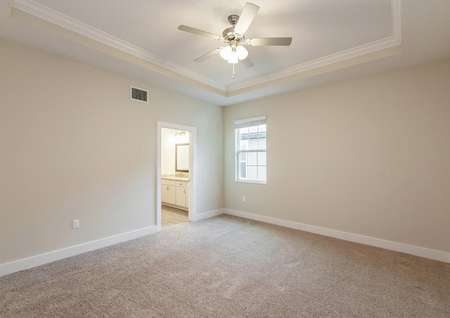 The primary bedroom features a vaulted ceiling, a ceiling fan and its own full bathroom with a walk-in closet.