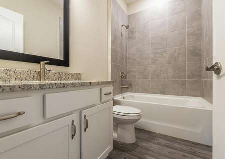 Guest restroom with granite countertops and modern hardware.