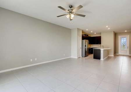 Patricio model home's open living room and kitchen. Tile flooring, fully upgraded kitchen and lots of space