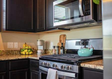 Staged kitchen with turquoise teapot on the stove, instant coffee maker, and utensils on the countertop