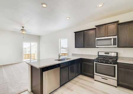 Beautiful kitchen with tall espresso cabinets and stainless steel appliances