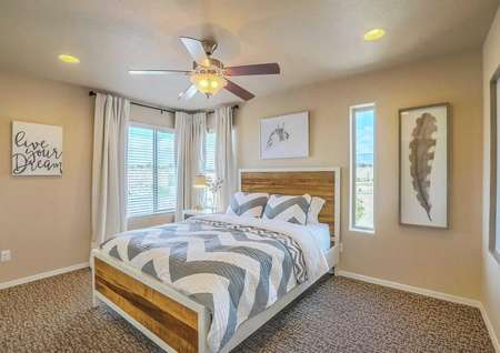 Sierra model home bedroom staged with wooden bed with grey striped comforter and pillows, artwork hanging on the walls, and overhead ceiling fan