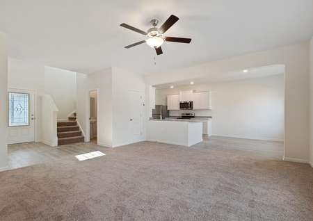 Spacious family room with carpet and ceiling fan opens to the dining room and kitchen to the right and a foyer to the left, with stairs leading to second floor.