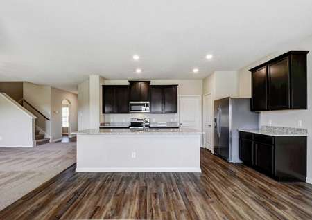 Shelby kitchen and dining area with dark wood flooring, gray countertops, and dark wood cabinets