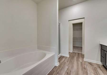 Master bathroom in the Oakmont floor plan with light vinyl flooring and large tub with separate shower with glass door and walk in closet