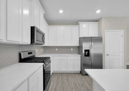 Stainless steel appliances, white cabinets and quartz countertops are found in this beautiful kitchen.