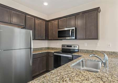 The kitchen comes with stainless steel appliances, tan granite and brown cabinetry.