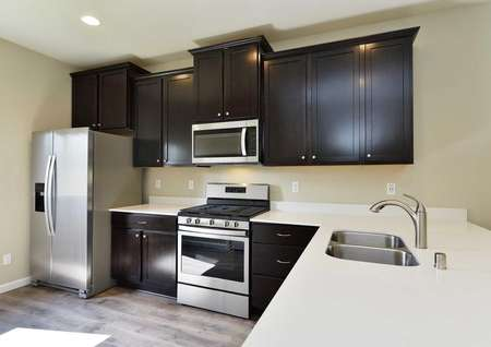 The Northwest Aspen kitchen showing stainless steel appliances and quartz countertops with dark brown cabinets.