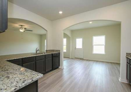Kitchen with vinyl wood-like flooring, granite counters, recessed lighting, and dark brown cabinets in the Rayburn floor plan
