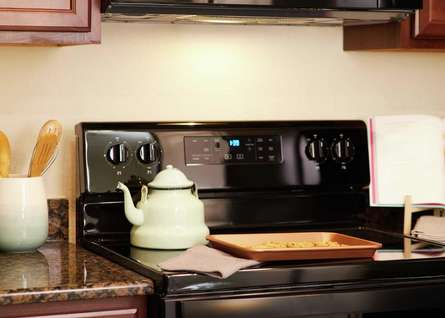 Trace kitchen with wooden cooking utensils, cookies in a tray, and white kettle on stovetop