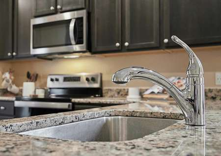 Kitchen sink, surrounded by granite countertops, with stainless steel appliances in the background.