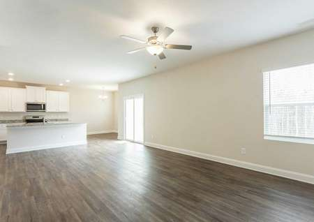 Hartford great room with wood flooring, white trim, and ceiling fan