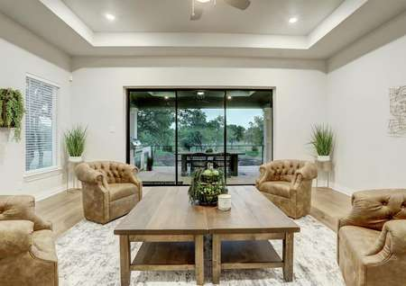 Staged sitting area with brown chairs, large coffee table and back yard views.