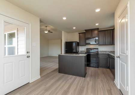 Sabine kitchen and dining nook with dark brown cabinets, recessed lights, and white backyard door with window