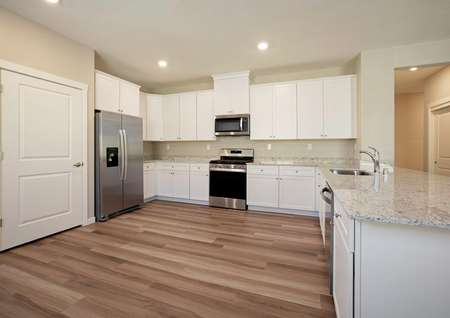 The spacious kitchen has white cabinetry, granite countertops, wood style flooring and more.