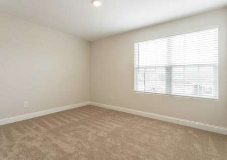 Avery bedroom with recessed lights, light brown carpeting, and large front-facing window